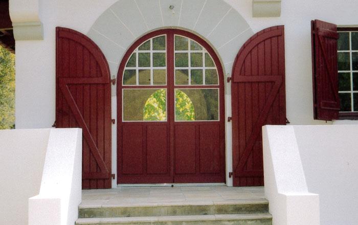 Création de portes vitrées pour une entrée voûtée avec volets assortis à la menuiserie